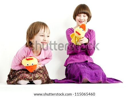two sisters with glove puppets - stock photo