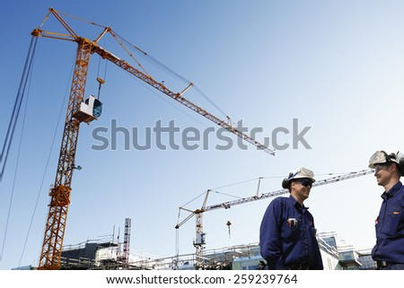 two site workers inside construction plant mobile cranes in background - stock photo