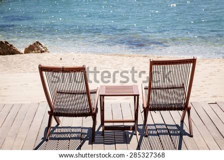 Two sitting place and table in a tropical beach - stock photo