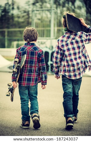 two skater boys walking towards half pipe,vintage effect added
