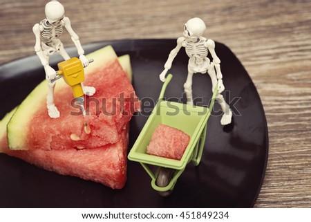 Two skeleton getting watermelon - stock photo