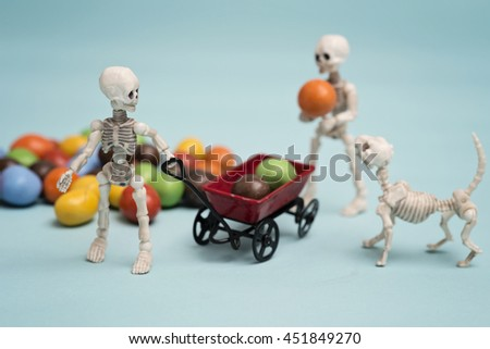 Two skeleton kids hauling chocolate candy  - stock photo