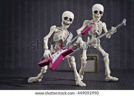 Two skeletons band playing rock music - stock photo