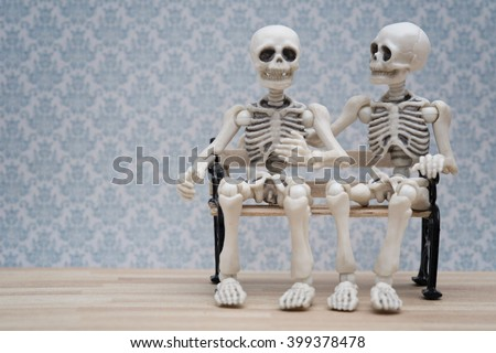 Two skeletons sitting on bench with blue background