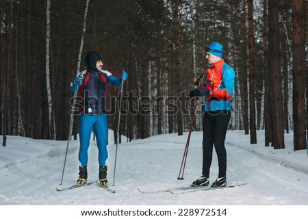Two skiers cross-country ski  talk in winter forest - stock photo