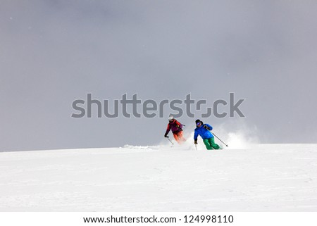 Two skiers in fresh powder snow, Utah, USA. - stock photo