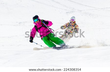 Two Skiers on mountain slope off piste quickly slide one after the other picking up snow dust - stock photo