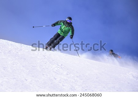 Two Skiers skiing downhill in high mountains and sunny day - stock photo