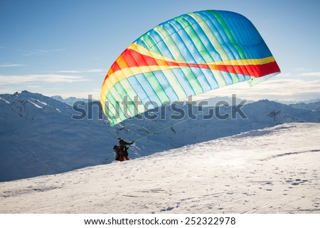 Two skiers taking off in a para-glider on a late afternoon in winter with the setting sun being hidden behind the parachute - stock photo