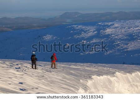 Two skiers walking snowy field at the mountain