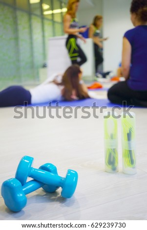 Two skipping ropes, dumbbells are on floor, three women are in hall for fitness out of focus