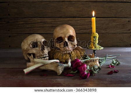 Two skull and bones with candle on the ole wood