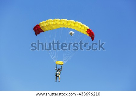 Two Skydiver with yellow parachute on blue sky. - stock photo
