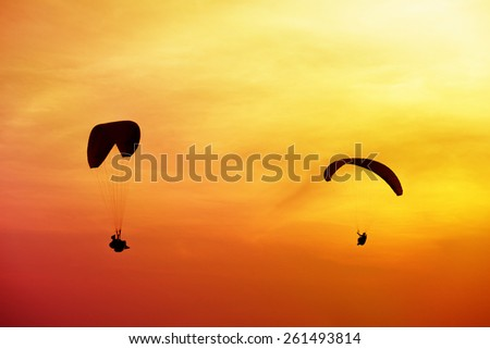Two skydivers flies on background of sunset sky - stock photo