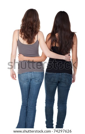 Two slender young women walking away, arm in arm.