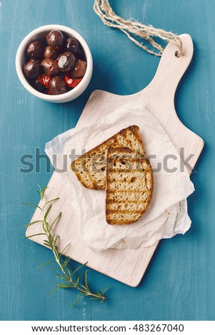 two slice of grilled bread with oil on a white chopping board, on a blue wooden table, with olives in a white bowl an rosemary