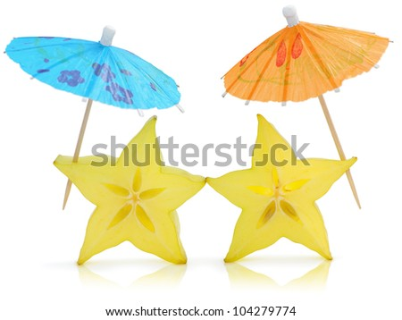 Two sliced starfruits with umbrellas isolated against white background