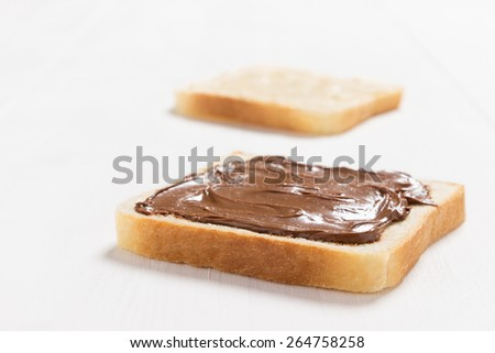 Two slices of bread with chocolate hazelnut  spread on white wooden table - stock photo