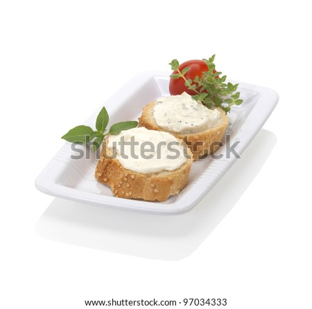 two slices of bread with spread cheese, decorated with a cherry tomato and herbs, on a white plate. - stock photo