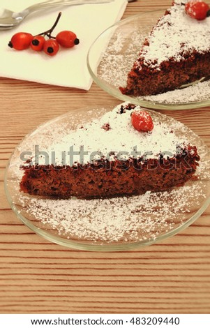 Two slices of chocolate cake and rose hips