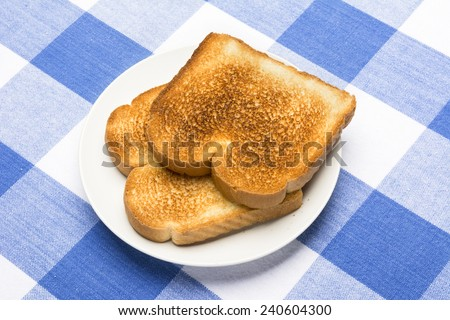 Two slices of fresh, white toast on a plate and checkered blue and white tablecloth  - stock photo