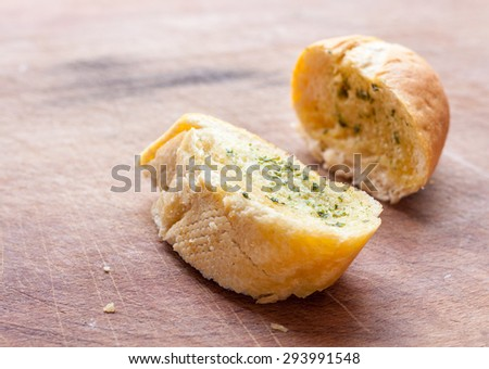 Two slices of garlic bread on a wooden surface - stock photo