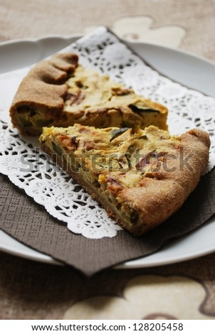 Two slices of vegetarian tart with zucchini, onion and tofu, selective focus - stock photo