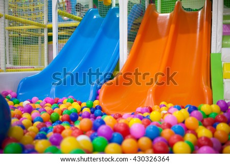 Two slide with colourful balls in the kid's playground. - stock photo