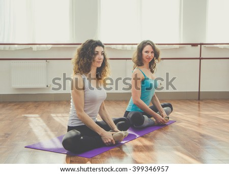 Two slim women are doing stretching