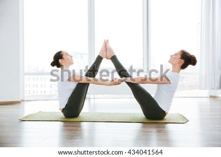 Two slim young women stretching legs on green yoga mat - stock photo