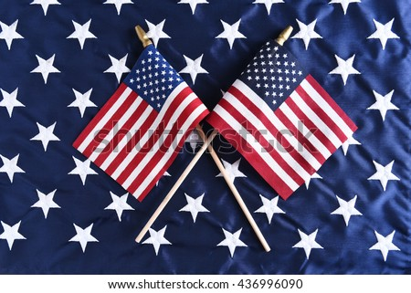 Two small American flags crossed on the star field of a larger flag. Perfect for Fourth of July or other patriotic American holidays. - stock photo