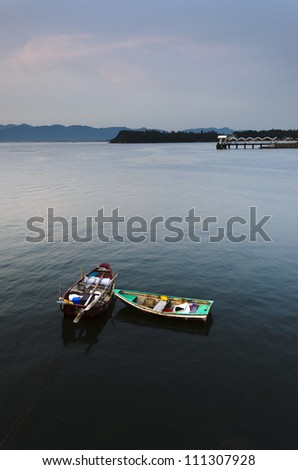 Two Small Boats and Public Pier in Calm Sea - stock photo