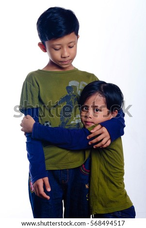 Two small boys happily playing and hugging each other isolated on white background