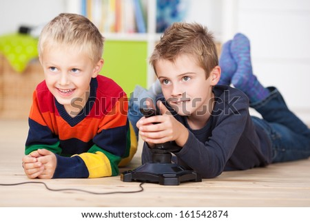 Two small boys lying side by side on their stomachs on the floor watching television and smiling happily at the programs - stock photo