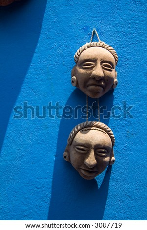 Two small ceramic masks hanging on a bright blue wall