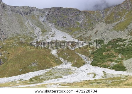 Two small Creeks are flowing down a mountain into the Lake Rifflsee in the Pitztal, in the Oetztal Alps. Tyrol, Austria, Europe.