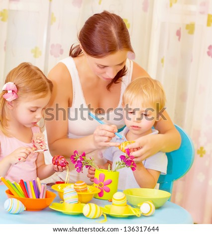 Two small cute children with beautiful mother paint Easter eggs at home, mom teaching babies decorate traditional eastertime symbol - stock photo