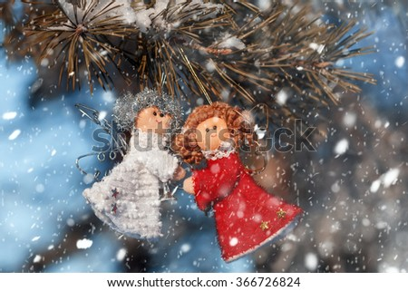 Two small dolls angels with sprig of pine sprinkled with snow. winter celebrations beautiful background.