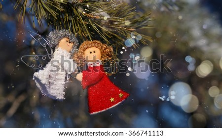 Two small dolls angels with sprig of pine sprinkled with snow. winter celebrations beautiful background