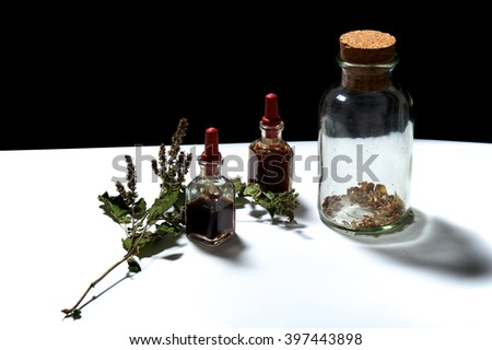 Two small eye dropper bottles with herbal extract essential oils and large jar with dried herbs and patchouli sprig.. Oils are patchouli and rosemary. - stock photo