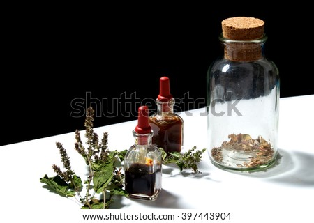Two small eye dropper bottles with herbal extract essential oils and large jar with dried herbs and dried branch from patchouli plant. Oils are patchouli and rosemary.