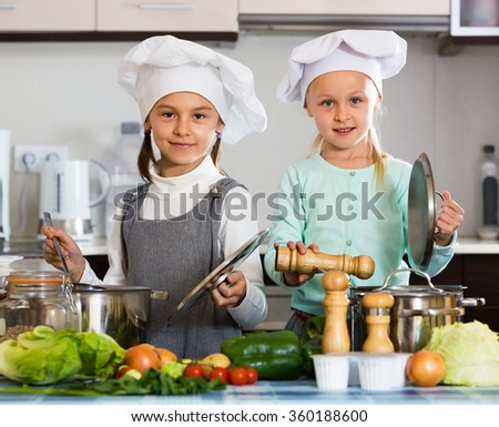 Two small girls cooking vegetable soup at home kitchen - stock photo