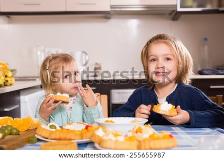 Two small girls eat yummy cream cakes at light kitchen