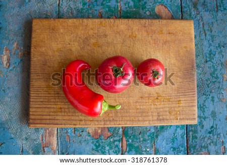 two small juicy tomatoes and peppers on a cutting board - stock photo