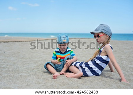 Two small kids sitting on the beach - stock photo