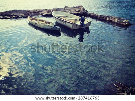 two small motor boats moored in the harbor of an island of the Dalmatian coast of Croatia. Vintage effect added.
