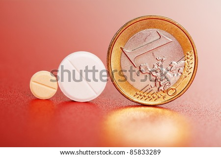 Two small pills standing beside one euro coin