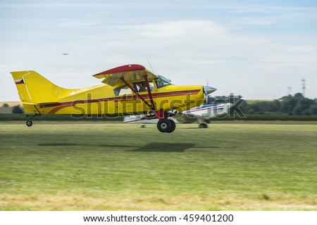 Two small planes start pulling on a grass runway airport. Towing planes taking off. All text and logos removed. - stock photo