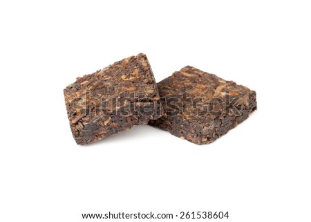 Two small pressing briquette of black Chinese Shu Pu Erh tea isolated on white background, selective focus with shallow DOF - stock photo