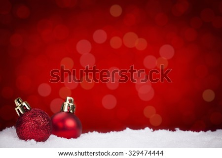 Two small red Christmas baubles on snow with defocused red lights in the background.